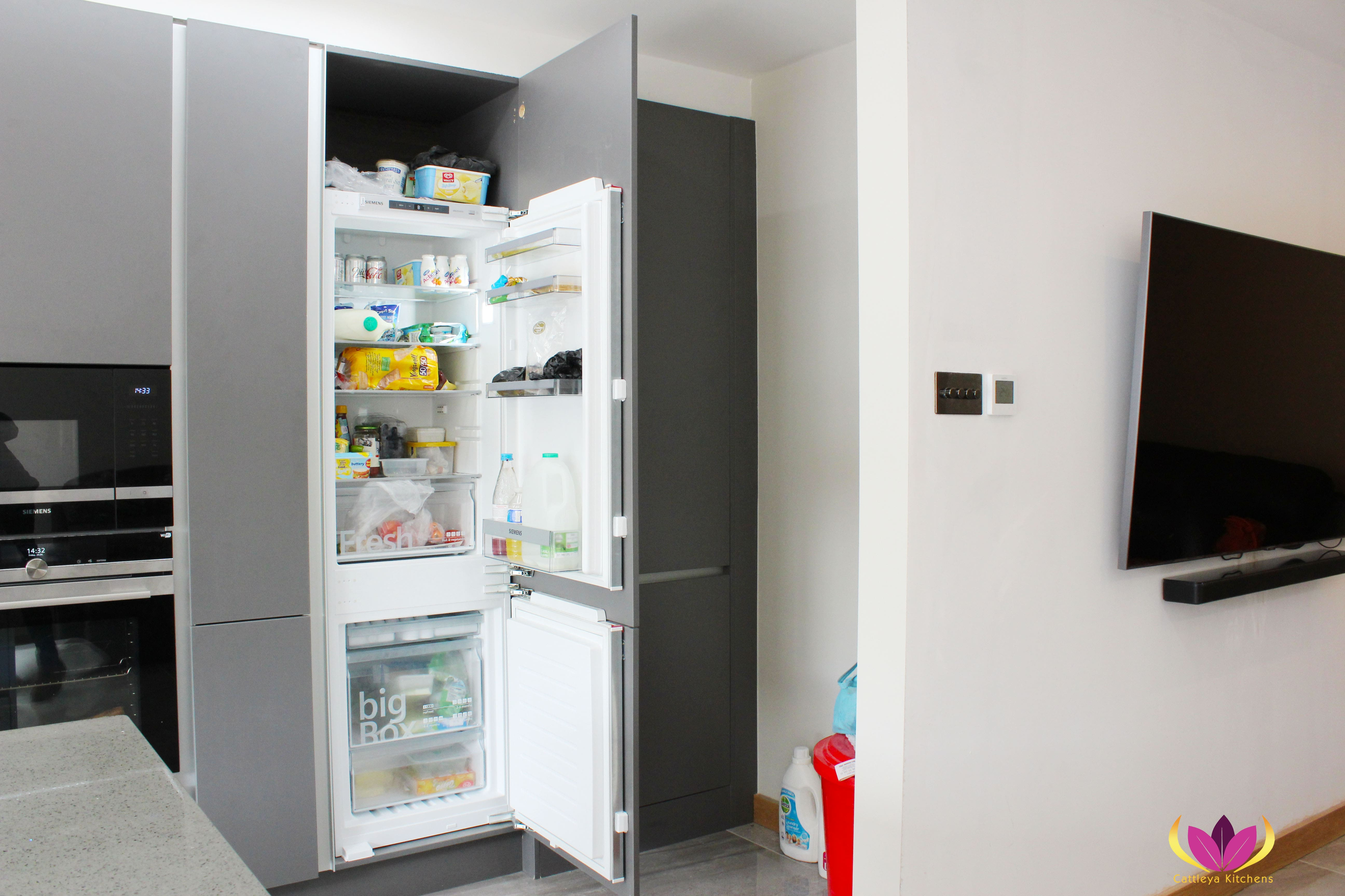 Refrigerator hidden inside gray cabinet Perivale Finished Kitchen Project